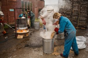 an artist in blue overalls and safety goggles and gloves is standing next to a metal bin with smoke coming out as they carry out Raku Firing at SSW
