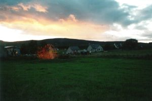 Picture of landscape with hills in the background and green grass in the foreground. There is a bonfire and the sky has pink and grey clouds