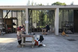 Two people working independently in a courtyard at heavy banker tables with stone carving tools.